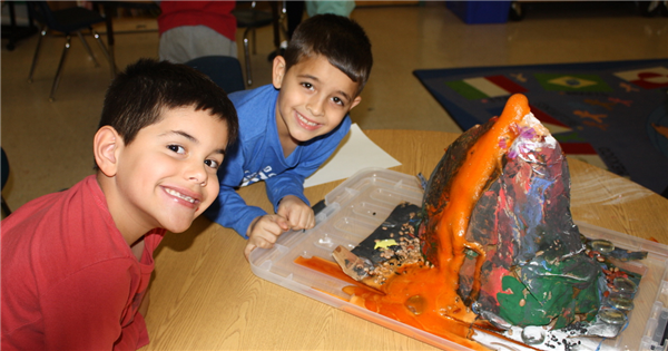 Two boys smiling in front of a volcano experiment.